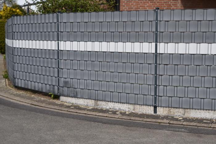 Ein Zaun mit Sichtschutzstreifen aus Plastik.