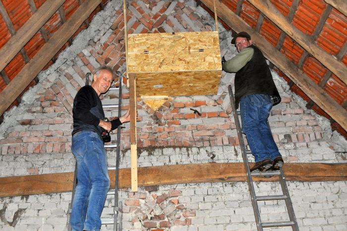 Zwei Mitglieder des BUND Warendorf hängen einen Eulenkasten auf.